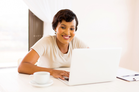 pretty young african woman working on laptop computer at home