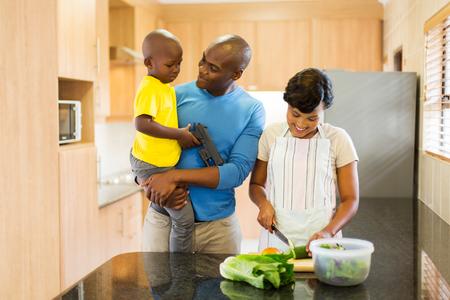 キッチンでサラダを作る幸せな若いアフリカ系アメリカ人家族 写真素材
