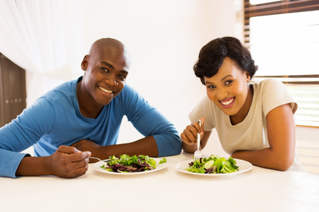to eat: portrait of young african american couple eating healthy salad for lunch
