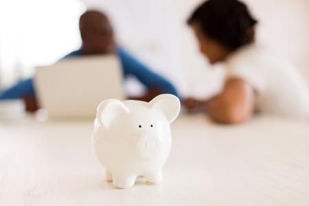 Nahaufnahme eines Sparschwein mit afrikanischen Paar auf dem Hintergrund