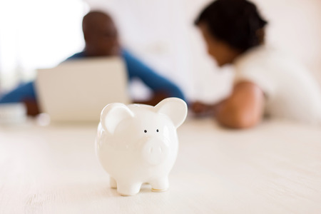 closeup of a piggybank with african couple on the background Foto de archivo