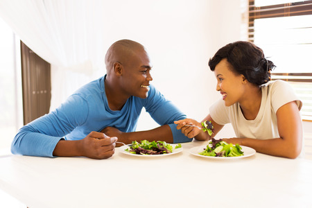 eating salad: smiling young african couple eating dinner together at home