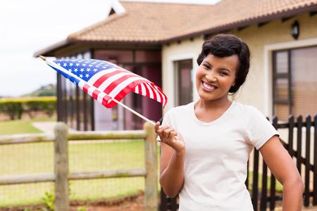 modelos posando: Retrato de la mujer bastante negro de la bandera de EE.UU. en el frente de su casa Foto de archivo