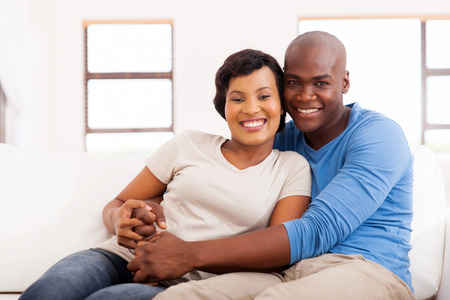 african american couple: portrait of happy african american couple sitting on sofa at home