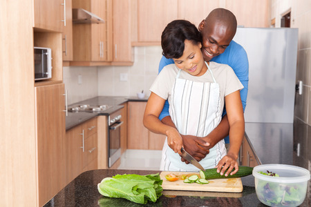 house wife: young african couple cooking in kitchen