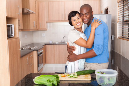 romantic african american couple embracing in kitchen