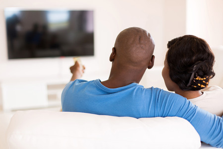 back view of young african couple watching tv in the living room at home 写真素材