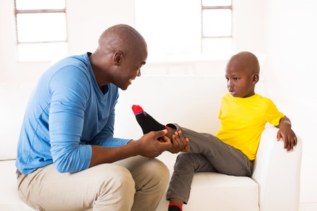 black  family: loving african man taking off sons socks
