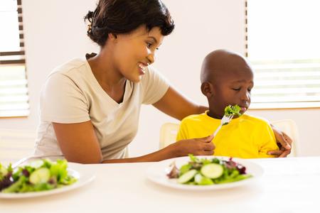 niños comiendo: madre bonita africano tratando de alimentar a su pequeño hijo que odia comer ensalada verde Foto de archivo