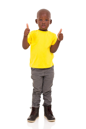 posing  agree: african american boy giving thumbs up on white background