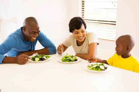 woman diet: happy african american family eating meal together Stock Photo