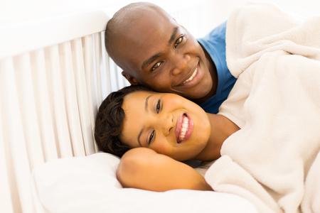pareja abrazada: Retrato de la feliz pareja africana joven en la cama
