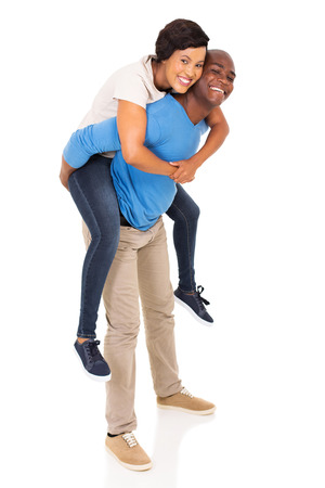 white playful: playful african american couple piggyback on white background Stock Photo