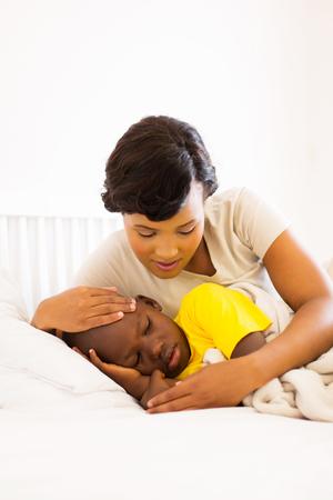 chory: kochająca afroamerykanin matka sprawdzania jej temperatury syna Zdjęcie Seryjne