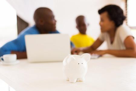 piggybank といくつかの金融計画をしているアフリカの家族をクローズ アップ 写真素材