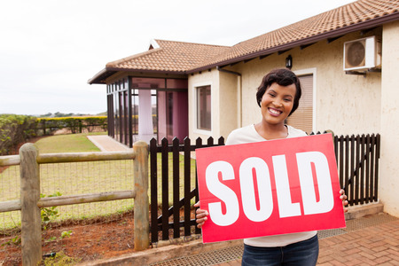 sold sign: happy african woman holding sold sign in front of house Stock Photo