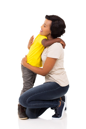 niño parado: little afro american boy hugging his pretty mother on white background