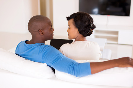 couple couch: lovely african american couple using laptop in living room