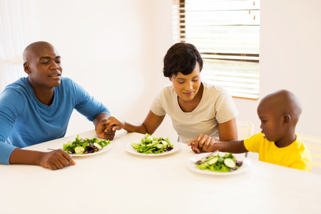 child sitting: young african family praying before having meal at home Stock Photo