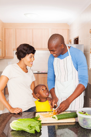 father and children: happy african american family of three cooking in home kitchen