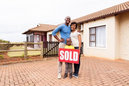 feliz familia africana joven delante de su casa con el signo de inmuebles vendidos Foto de archivo