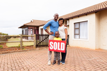 Gelukkig jonge Afrikaanse familie in de voorkant van hun huis met verkocht onroerend goed teken Stockfoto