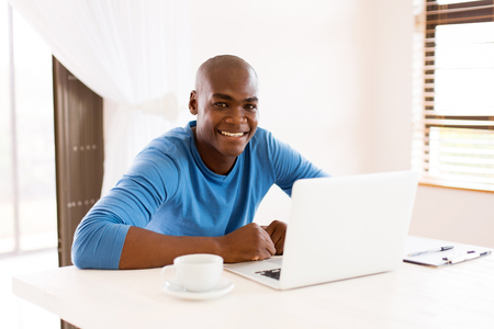 black guy: happy african man using laptop computer at home