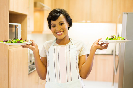 cheerful: portrait of cheerful young african woman holding plates with salad