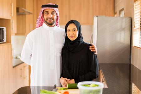 arab adult: happy muslim couple in kitchen