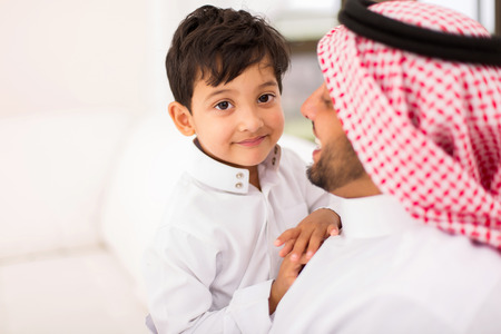 adorable little Arabian boy and his father relaxing at home