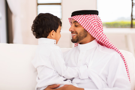 middle eastern ethnicity: portrait of happy arabian father and son sitting at home