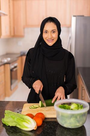 arabian food: happy young arabian woman cooking dinner