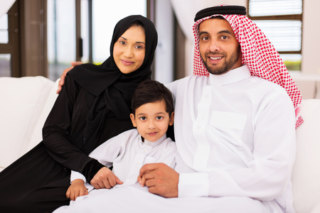 beautiful young arabian family sitting on sofa at home