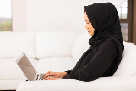 middle eastern woman: pretty young middle eastern woman using laptop at home Stock Photo