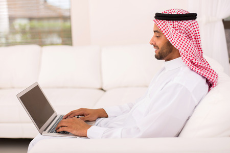agal: young muslim man using laptop at home