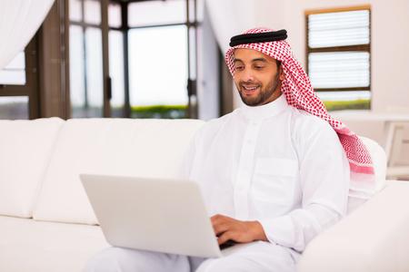 Moderní mladý arabský muž pomocí přenosného počítače doma