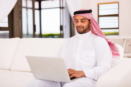 modern young arabian man using laptop computer at home