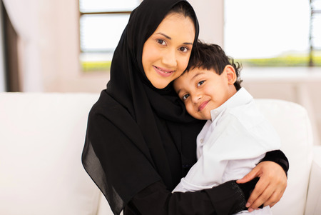 attractive young muslim woman sitting on couch with her son