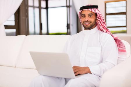 buen vivir: apuesto hombre islámico usando la computadora portátil en la sala de estar Foto de archivo