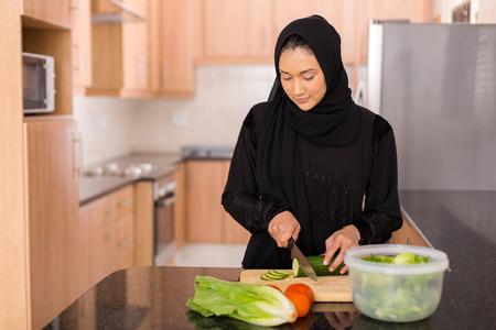 arabian food: pretty muslim woman chopping vegetables in kitchen