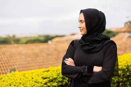 thoughtful young muslim woman with arms crossed
