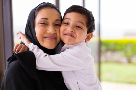 niño de pie: muchacho musulmán linda que abraza a su madre Foto de archivo