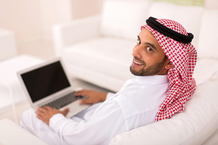 agal: happy young arabian man with laptop looking back