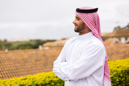 arms folded: handsome Arabian man looking away