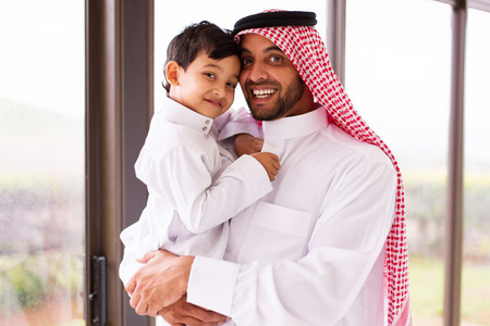 agal: happy muslim father and son indoors