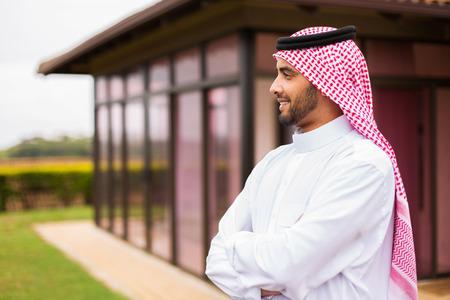 Hombre árabe pensativo de pie en frente de su casa Foto de archivo
