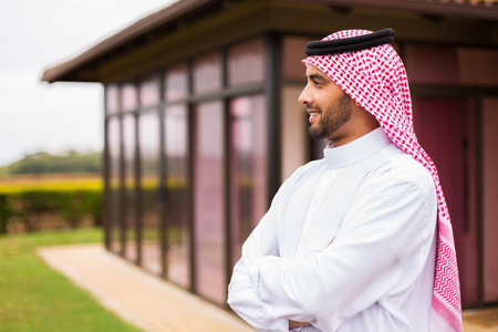 man head: thoughtful arabian man standing in front of his house