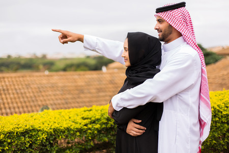 thobe: cheerful young middle eastern couple pointing outside their house
