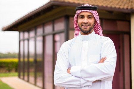 muslim: modern young arabian man with arms crossed outside his house