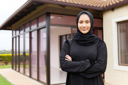 middle eastern woman: beautiful middle eastern woman standing in front of her house Stock Photo
